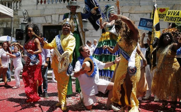 """Rio de Janeiro's Mayor Eduardo Paes (C) kneels next to the """"Rei Momo"""", or Carnival King Wilson Neto (2nd L), as they pose during the handing over of the ceremonial key to the city at the Cidade Palace in Rio de Janeiro, Brazil, February 5, 2016. The event officially kicks off the 2016 carnival week in Rio. REUTERS/Sergio Moraes"""