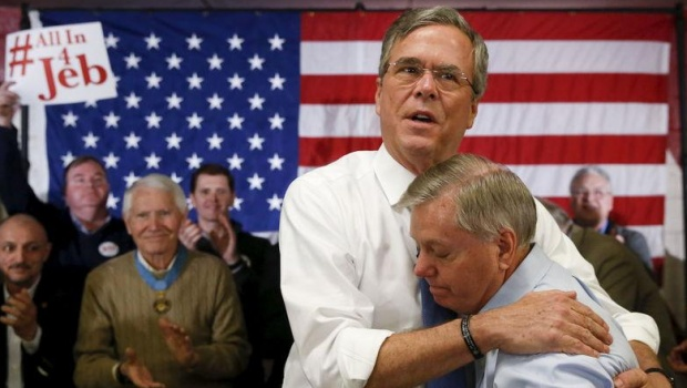 Jeb Bush embraces Lindsey Graham after Graham introduced him at a town hall during a campaign stop at Woodbury School in Salem, February 7, 2016. REUTERS/Adrees Latif .