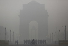 A man rides his bicycle next to soldiers marching in front of India Gate on a smoggy morning in New Delhi, December 1, 2015. REUTERS/Anindito Mukherjee/Files
