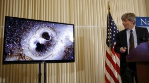 Dr. David Reitze, Executive Director of the LIGO Laboratory at Caltech, shows the merging of two black holes at a news conference to discuss the detection of gravitational waves, ripples in space and time hypothesized by physicist Albert Einstein a century ago, in Washington February 11, 2016. REUTERS/Gary Cameron