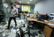 An employee walks on newspapers after protesters attacked the office of Saudi-owned newspaper Asharq al-Awsat in Beirut, Lebanon, in this April 1, 2016 file photo.  REUTERS/Mohamed Azakir/Files