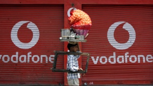 "A vendor selling ""paani puri"", a traditional Indian snack, walks past closed shops displaying an advertisement for Vodafone in Jammu May 22, 2012.  REUTERS/Mukesh Gupta/File photo"