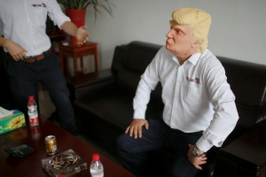 "The manager of Jinhua Partytime Latex Art and Crafts Factory wears a mask of U.S. Republican presidential candidate Donald Trump as he poses after talking to reporters in Jinhua, Zhejiang Province, China, May 25, 2016. There's no masking the facts. One Chinese factory is expecting Donald Trump to beat his likely U.S. presidential rival Hilary Clinton in the popularity stakes. At the Jinhua Partytime Latex Art and Crafts Factory, a Halloween and party supply business that produces thousands of rubber and plastic masks of everyone from Osama Bin Laden to Spiderman, masks of Donald Trump and Democratic frontrunner Hillary Clinton faces are being churned out. Sales of the two expected presidential candidates are at about half a million each but the factory management believes  Trump will eventually run out the winner. ""Even though the sales are more or less the same, I think in 2016 this mask will completely sell out,"" said factory manager Jacky Chen, indicating a Trump mask. REUTERS/Aly Song"