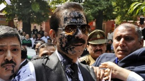 Sahara group chairman Subrata Roy (C) has his face smeared in ink thrown by an unidentified man upon his arrival at the Supreme Court in New Delhi, March 4, 2014. REUTERS/Stringer/File Photo