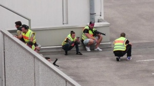A screen grab taken from video footage shows plain clothes police officers taking cover in the car park of the Olympia shopping mall during shooting rampage in Munich, Germany July 22, 2016.  dedinac/Marc Mueller/handout via REUTERS