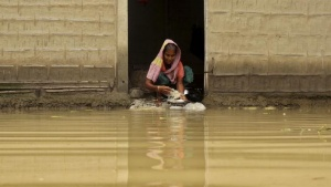 REPRESENTATIVE PHOTO: A woman washes utensils with floodwater at the entrance of her house in a flooded neighbourhood after incessant rains at Bullut village in Kamrup district in the northeastern state of Assam, India, June 12, 2015. REUTERS/Stringer