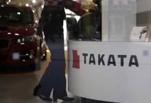 FILE PHOTO: A woman stands next to a logo of Takata Corp at a showroom for vehicles in Tokyo, Japan, November 6, 2015. REUTERS/Toru Hanai/File Photo