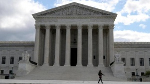 FILE PHOTO: A person walks outside the U.S. Supreme Court in Washington, U.S., May 12, 2020. REUTERS/Leah Millis/File Photo