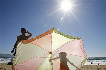 A boy casts a shadow on an umbrella as he stands next to his father on a beach in Vina del Mar city, northwest of Santiago, December 28, 2006. The Chilean coasts are experiencing a heat wave, with radiation rising to dangerous levels. REUTERS/Eliseo Fernandez