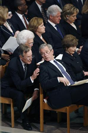 U.S. President George W. Bush (C) talks with his father, former President George Bush (L), during former U.S. President Gerald Ford's state funeral at the National Cathedral in Washington January 2, 2007 file photo. Bush's father accused the news media of ''personal animosity'' toward his son and said he found the criticism so unrelenting he sometimes talked back to his television set. REUTERS/Jim Bourg