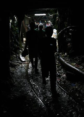 Miners walk inside a mine in Mount Diwata, Monkayo town, Composetela Valley, 600 miles (965 kilometres) south of Manila, in this February 9, 2007 file photo. The lure of gold has attracted tens of thousands small-scale miners to Mount Diwata, an infamous gold rush area commonly known as Diwalwal, transforming a once uninhabited wilderness to a rubble-strewn settlement where processing waste has killed the local river. Most of the fortune-hunters live a dangerous, hand-to-mouth existence, forced to process the ore in mercury-filled drums under their houses and risking cave-ins underground. REUTERS/Cheryl Ravelo/Files