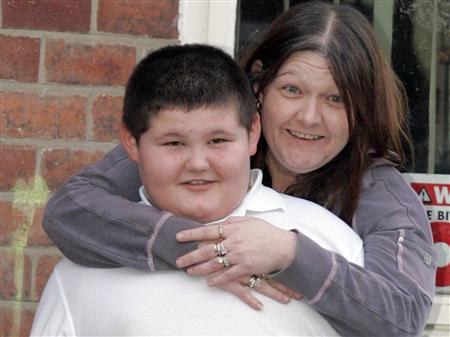 Connor McCreaddie (L), eight, and his mother Nicola McKeown pose for photographers outside their home in Wallsend, northern England February 26, 2007. British social workers decided on Tuesday to allow an eight-year-old boy who weighs almost 200 lb (90 kg) to remain at home with his mother, even though she has refused to stop feeding him junk food. REUTERS/Nigel Roddis