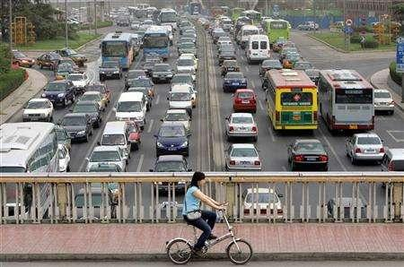 A woman rides her bicycle during rush hour in Beijing, May 17, 2006. China, where bicycles once ruled the road in swarms and still just about outnumber bicycle thieves, is cracking down on bicycle theft, offering rewards for tip-offs on offenders. REUTERS/Jason Lee
