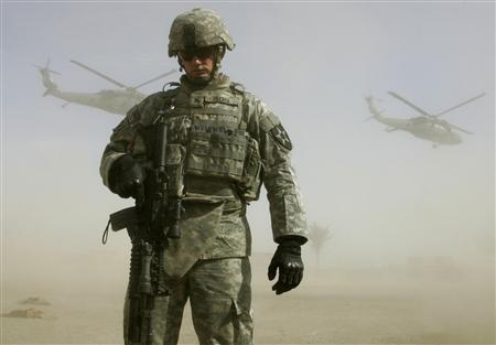 A U.S. soldier of the 3rd Squadron 61st Cavalry Regiment shields himself from the dust as Blackhawk helicopters take off south of Baghdad, March 5, 2007. REUTERS/Fabrizio Bensch