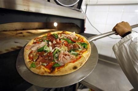 A pizza is removed from an oven in a file photo. A New York restaurateur has cooked up the most world's most extravagant pizza -- a $1,000 pizza topped with six sorts of caviar and fresh lobster. REUTERS/Eric Gaillard