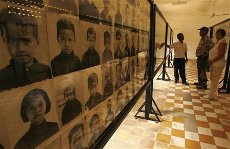 Tourists look at pictures of child victims of the Khmer Rouge on display at the Toul Sleng genocide museum in Phnom Penh March 15, 2007. REUTERS/Chor Sokunthea