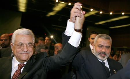 Palestinian President Mahmoud Abbas (L) and Prime Minister Ismail Haniyeh raise their hands before Haniyeh's speech to parliament in Gaza March 17, 2007. Palestinian leaders struck discordant notes on how to deal with Israel on Saturday as parliament met to usher in a unity government intended to halt factional fighting and ease a crippling Western aid embargo. REUTERS/Suhaib Salem