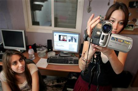 Lital Mizel (L) watches Adi Frimmerman use a video camera at Lital's house in the central Israeli town of Ramle, October 12, 2006. The two 22-years-olds titled a video clip they put together for a boyfriend's birthday as ''Dancing stupid'' and posted it on the YouTube website. The video has since become an Internet hit. Next week, YouTube will present awards for best user-generated videos of 2006. REUTERS/Yonathan Weitzman