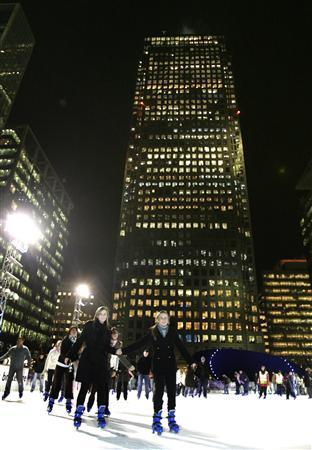 In this file photo people ice skate beneath office blocks at Canary Wharf in London December 27, 2006. Songbird Estates, which owns the majority of office buildings in London's Canary Wharf, said net asset value rose 48 percent, thanks to higher occupancy levels and strong valuation uplift. REUTERS/Luke MacGregor