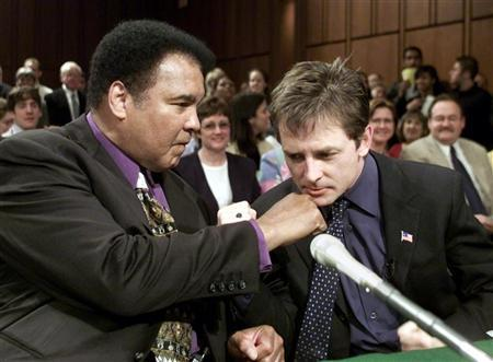 Boxing legend Muhammad Ali (L) pretends to punch actor Michael J.Fox before a Senate subcommittee hearing on Parkinson's Disease on Capitol Hill in Washington in this May 22, 2002 file photo. U.S. government researchers launched a trial on Thursday testing creatine, a supplement sold to improve exercise performance, against Parkinson's disease. REUTERS/William Philpott WP