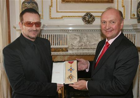 Bono (L) is presented with his honorary knighthood by British Ambassador David Reddaway at the ambassador's official residence in Sandyford, Dublin March 29, 2007. The U2 singer accepted the award in recognition of his outstanding contribution to music and remarkable humanitarian work. REUTERS/Julien Behal/PA/WPA Pool