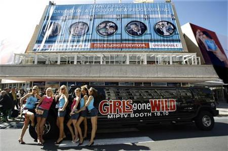 Performers of adult entertainment video ''Girls Gone Wild'' pose in front of the festival palace where the MIPTV, the International Television Programs Market is held in Cannes, in this file photo from April 3, 2006. Having made a fortune off bare-breasted women, ''Girls Gone Wild'' founder Joe Francis is setting his sights on selling another type of breast. REUTERS/Eric Gaillard