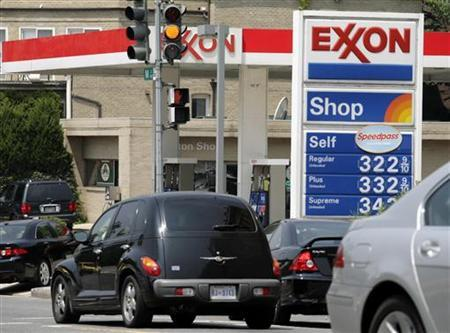 Cars line up at a gas station in Washington July 27, 2006. The world's five largest fully publicly traded oil firms are planning to invest billions of dollars more this year but extra spending may not translate into higher production. REUTERS/Yuri Gripas