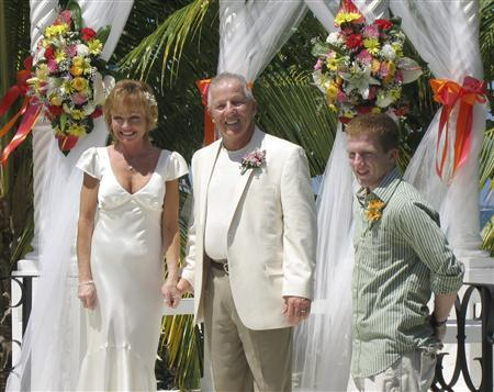 Gerri and Paul Carr, with Paul's son Patrick Carr at right, poses in Negril Jamaica March 17, 2007. The first time Gerri Carr got married, she took a traditional route -- big Catholic church, packed pews, and a near panic attack before she walked down the aisle. Last month, Carr, 41, marked the milestone of a second marriage under a breezy blue Jamaican sky, surrounded by two dozen friends and family members, soft white sand and the pulse of ocean waves. REUTERS/Michael Heart/Handout