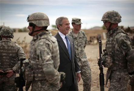 U.S. President George W. Bush laughs among soldiers during his visit to the National Training Center at Fort Irwin in the Californian desert, April 4, 2007. The U.S. Defense Department is preparing to send another 12,000 National Guard combat troops to Iraq, NBC Nightly News reported on Thursday, citing Pentagon sources. REUTERS/Jason Reed