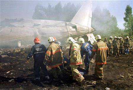 Russian emergency workers carry a body from the wreckage of a Russian Ilyushin Il-86 passenger plane belonging to the Pulkovo Airline that crashed on take-off from Moscow's Sheremetyevo airport, in this July 28, 2002 file photo. Russia remains the most dangerous place to fly despite global improvements that made 2006 the safest year on record, the International Air Transport Association (IATA) reported on Tuesday. REUTERS/Stringer