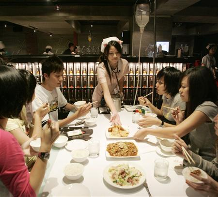 A waitress dressed as a nurse serves food to customers at a hospital-style restaurant in Taipei April 20, 2007. REUTERS/Richard Chung