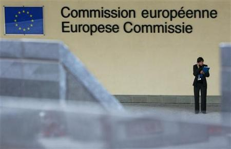 A woman uses her cell phone as she stands outside the entrance of the European Commission headquarters in Brussels, July 26, 2005. EU politicians and officials on Tuesday failed to resolve key details of a plan to cut the cost of calling abroad on cell phones, EU sources said. REUTERS/Thierry Roge