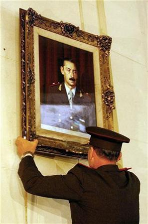 An Argentine Army official takes down the portrait of former dictator Jorge Rafael Videla from one of the galleries of the Argentine Colegio Militar (Military School) in Buenos Aires, March 24, 2004. A federal court on Wednesday struck down a presidential pardon and restored human rights abuse convictions for two leaders of Argentina's 1976-83 military dictatorship. The ruling forces former Gen. Jorge Videla and former Adm. Emilio Massera to serve out life sentences handed down in 1985 after they were convicted of devising a systematic plan by the military to abduct, torture and execute suspected opponents of the regime. REUTERS/Stringer