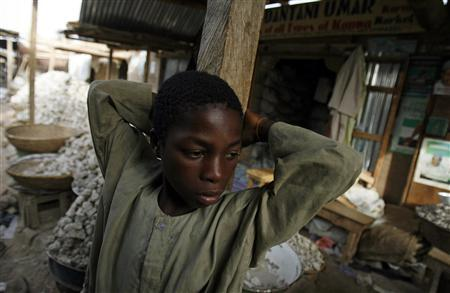 A boy rests is front of shops in the old market of Kano April 24, 2007. Many working children in towns are engaged in different activities like street traders or apprentices to artisans and most start working between the ages of five and nine and continued into adulthood. REUTERS/Radu Sigheti