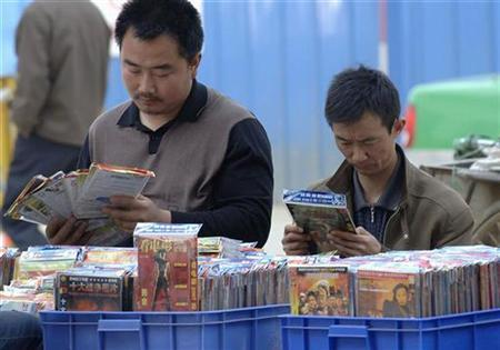 Two men select pirated DVDs along a street in Hefei, Anhui province April 25, 2007. China and Russia again lead the United States' annual list of the world's biggest producers of pirated and counterfeited goods, a U.S. trade report said on Monday. REUTERS/Jianan Yu
