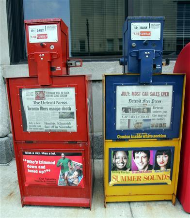 A Detroit News (L) and Detroit Free Press newspaper box sit in front of the newspapers building in downtown Detroit, Michigan August 3, 2005. REUTERS/Rebecca Cook