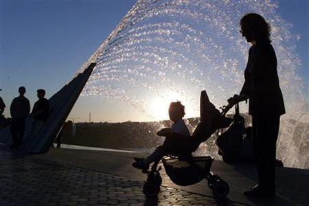 A woman walks her child past a fountain in an undated file photo. If the typical stay-at-home mother in the United States were paid for her work as a housekeeper, cook and psychologist among other roles, she would earn $138,095 a year, according to research released on Wednesday. REUTERS/Ali Jarekji