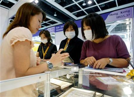 A shop assistant in Hong Kong serves customers from Japan after the WHO lifted its SARS travel warning on the city, June 20, 2003. Face masks may do little to prevent infection during an influenza pandemic, but wearing them might help comfort people in crowds, the Centers for Disease Control and Prevention said on Thursday. REUTERS/Kin Cheung