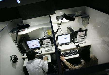 Men make use of the internet service in the private rooms of an internet cafe in Tokyo May 2, 2007. Some low-wage earning young people who cannot afford apartments in Tokyo are choosing to live in internet cafes, which are cheaper than a hotel and even offer showers, microwaves and large libraries of manga to read. Picture taken May 2, 2007. REUTERS/Kim Kyung-Hoon