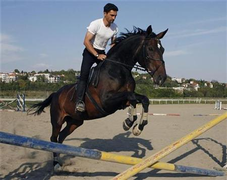 In this file picture, a man trains his horse at Belgrade's hippodrome, April 18, 2007. The Rolling Stones have asked to change the venue for a concert in Belgrade to spare hundreds of horses from enduring a potentially traumatic experience. REUTERS/Ivan Milutinovic