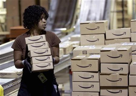 A worker loads a shipment of outgoing boxes at the Amazon.com warehouse facility in New Castle, Delaware, November 24, 2006. Amazon.com Inc. said on Wednesday the company will launch a digital music store later in 2007 with millions of songs, free of copy protection technology that limits where consumers can play their music. REUTERS/Tim Shaffer
