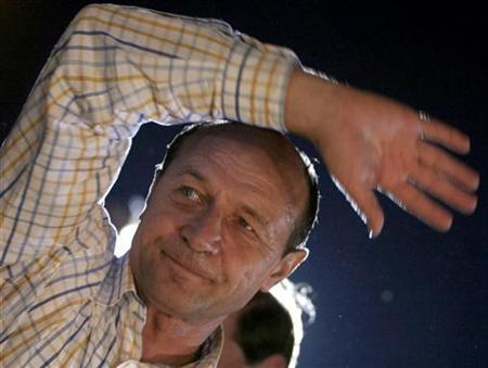 Romania's President Traian Basescu gestures to his supporters after the first exit polls during an impeachment referendum in Univercity square in Bucharest May 19, 2007. Romanians rejected an attempt by parliament to impeach reformist President Traian Basescu in the Saturday referendum, official results showed on Sunday, giving fresh support to his anti-sleaze campaign. REUTERS/Mihai Barbu