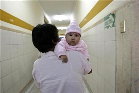 File photo shows a grandmother carrying her new born granddaughter on the way to an appointment with a doctor in Lima's maternity hospital, May 10, 2007. Alternatively, free- or unassisted birth means having a baby with no medical or professional help. In Britain, as in North America, where its popularity is growing, it is legal as long as delivery is not ''assisted'' by an unqualified partner, friend or husband. REUTERS/Enrique Castro-Mendivil