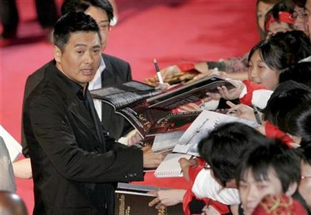 File photo shows Hong Kong actor Chow Yun-Fat (L) giving his autographs to fans during the Asian premiere of his new movie ''Pirates of the Caribbean: At World's End'' in Tokyo May 23, 2007. REUTERS/Toru Hanai