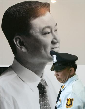 A security guard stands next to a portrait of ousted Prime Minister Thaksin Shinawatra displayed at Thai Rak Thai party headquarter in Bangkok May 29, 2007. Thai judges said on Wednesday the party of Thaksin was guilty of the first of two charges of election breaches which could see his party disbanded and its top officials barred from politics. REUTERS/Chaiwat Subprasom