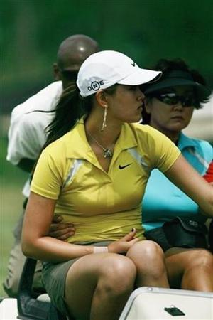 Michelle Wie (L) rides back to the clubhouse in a cart with her mother Bo after withdrawing from the first round of the Ginn Tribute Hosted by Annika golf tournament in Mt. Pleasant, South Carolina, May 31, 2007. A row between the world's two best known women golfers is raising the temperature for this week's LPGA Championship, with Annika Sorenstam saying Wie lacked class in dealing with a wrist injury. REUTERS/Tami Chappell