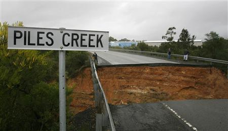 Three people inspect a collapsed section of the Pacific Highway that runs over Piles Creek near Somersby north of Sydney June 9, 2007. The death toll from a violent storm and torrential rain lashing Australia's east coast rose to six, police said on Saturday, as residents braced for a second turbulent night. REUTERS/Tim Wimborne