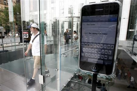 A passer-by walks near a replica display of Apple's iPhone at the Fifth Avenue Apple store in New York, June 25, 2007. The music industry has long hoped mobile phones will help turn around weak music sales, but music executives privately fear the most obvious contender, the iPhone, may give too much clout to Apple Inc. <AAPL.O>, in shaping the future of the fledgling mobile music market. REUTERS/Keith Bedford