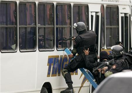 Police officers attempt to free hostages in a bus in Rio de Janeiro, November 10, 2006. A Brazilian woman whose estranged husband held her hostage at gunpoint on a bus for 10 hours along with dozens of passengers last year has decided to reunite with him. REUTERS/Bruno Domingos