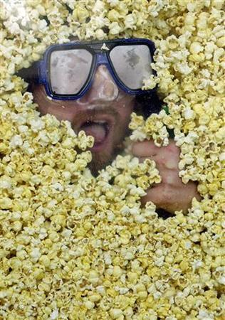 A competitive eater tries to eat his weight in popcorn in New York, May 3, 2004. U.S. popcorn prices have risen more than 40 percent since 2006 as soaring demand for feed corn to fuel the ethanol boom has spilled over into the favorite snack of American movie-goers. REUTERS/Chip East